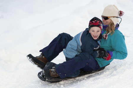 preadolescent: Mother and son sledding