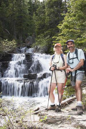 Couple hiking near a waterfall 스톡 콘텐츠