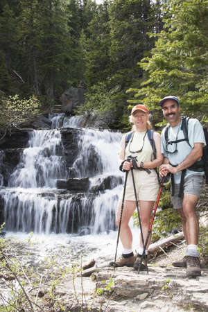 caucasian ancestry: Couple hiking near a waterfall Stock Photo