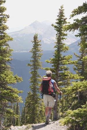 kananaskis country, alberta, canada; a male hiker walking down a trail at nahahi ridge photo