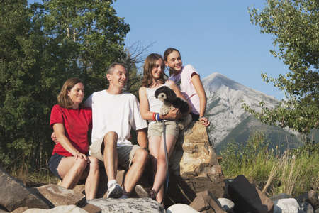 caucasian ancestry: kananaskis country, alberta, canada; a family sitting on the rocks in the mountains with their dog