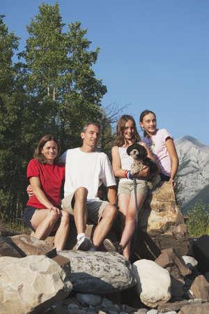 jeune fille adolescente: pays de Kananaskis, alberta, canada ; une famille assis sur les rochers dans les montagnes avec leur chien.