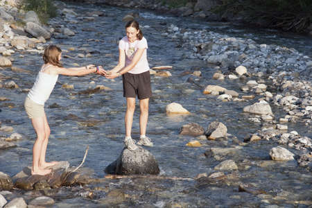 kananaskis country, alberta, canada; two girls playing on the rocks in the river Stock Photo - 7191341