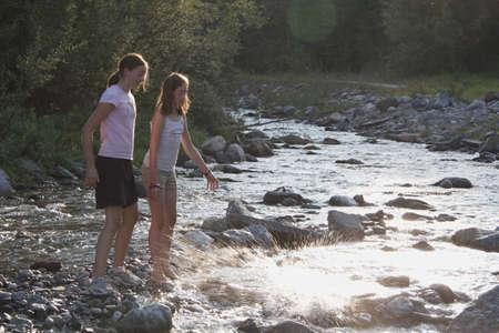 sweet seventeen: kananaskis country, alberta, canada; two girls throwing rocks into the river