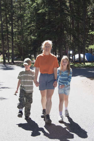 preadolescent: banff national park, alberta, canada; a woman walks with a boy and girl in a campground