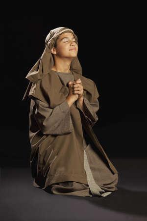 ひざまずく: 若いイエスを描いた少年