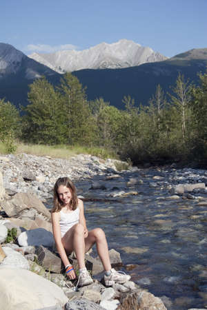 kananaskis country, alberta, canada; a girl sits by the river in the mountains photo
