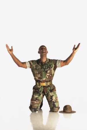 ひざまずく: フォートローダーデール、フロリダ州、アメリカ合衆国アメリカ;空気と上方への検索で腕と軍の男性