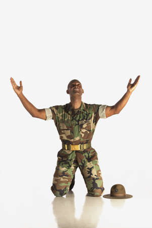 kneeling: fort lauderdale, florida, united states of america; a military man with arms in the air and looking upwards
