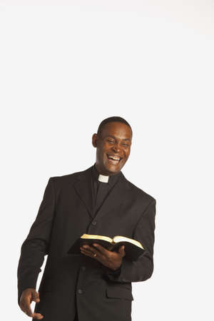 a man wearing a clerical collar and laughing while holding an open bible photo