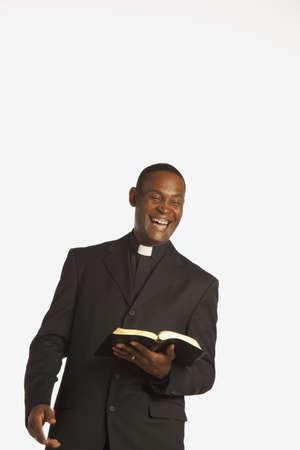 low angle views: un hombre llevando un collar clerical y riendo mientras mantiene una Biblia abierta