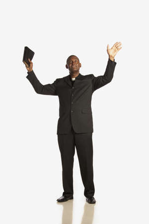 a man wearing a clerical collar and holding his bible up with hands raised and looking up photo