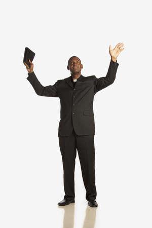pr�tre: un homme portant un collier de commis aux �critures et brandissant sa bible de mains soulev�es et regardant