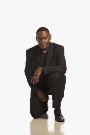 a man wearing a clerical collar kneeling in prayer