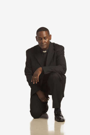 a man wearing a clerical collar kneeling in prayer photo