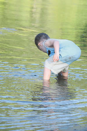 cahill: a young boy playing in the shallow water