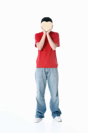 cahill: a boy with a heart covering his face Stock Photo