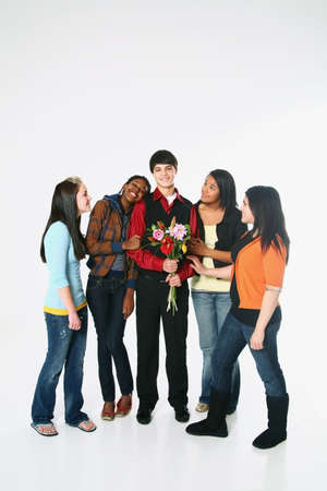 girls surrounding a boy who is holding flowers photo