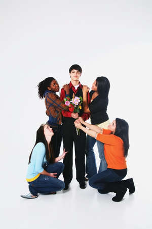girls surrounding a boy who is holding flowers Stock Photo - 7191708