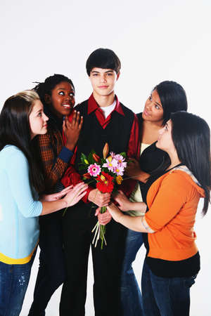 pre adolescence: girls surrounding a boy who is holding flowers Stock Photo