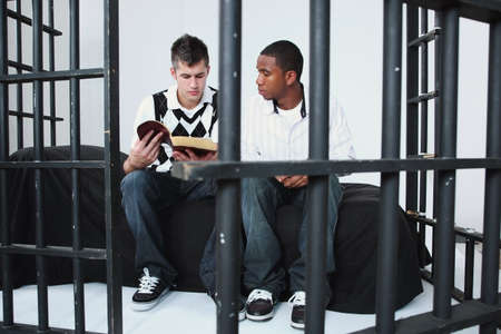 vertical bars: a young man reading the bible to another young man in jail