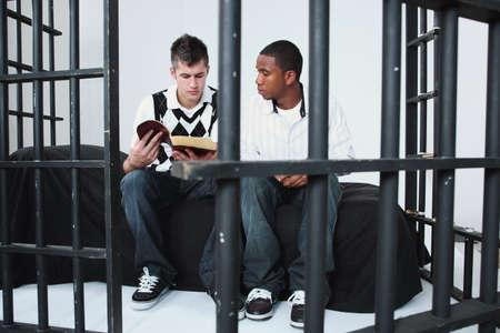 strafgefangene: ein junger Mann, das Lesen der Bibel, ein anderer junger Mann im Gef�ngnis  Lizenzfreie Bilder