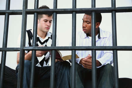delincuencia: un hombre joven Lee la Biblia a otro joven en la c�rcel  Foto de archivo