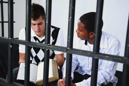 een jonge man leest de Bijbel aan een andere jonge man in de gevangenis  Stockfoto