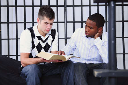 a young man reading the bible to another young man in jail