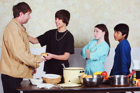 ambivalence: teenagers with differing attitudes serving a meal to a man
