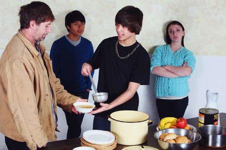 vagabundos: adolescentes que sirve una comida a un hombre  Foto de archivo