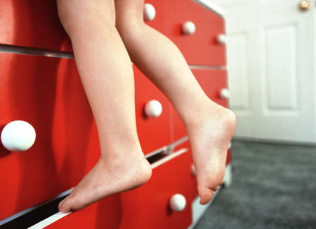 naughty girl: Close-Up of Girls Feet Climbing Dresser Stock Photo