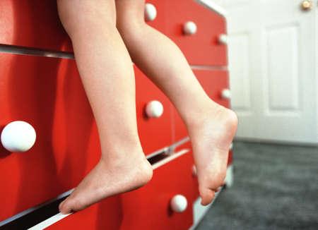 girls feet: Close-Up of Girls Feet Climbing Dresser Stock Photo