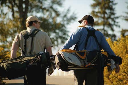 golf cap: Two men carry golf bags Stock Photo