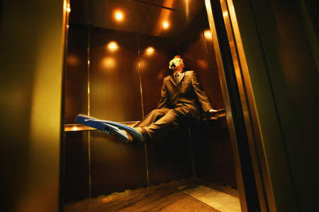 flippers: Businessman with flippers & goggles on in elevator