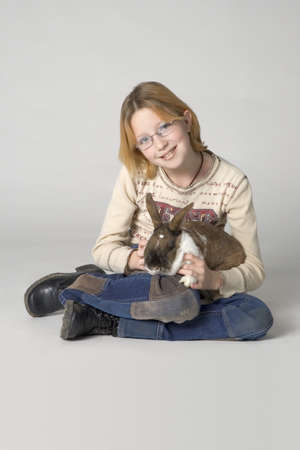 children  play: Young girl with pet rabbit