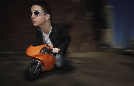 mini bike: Bizarre image of man riding on a mini motorcycle Stock Photo