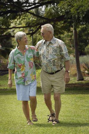 Senior couple walking in field photo