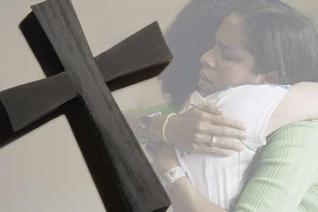 Women hugging, cross Imagens