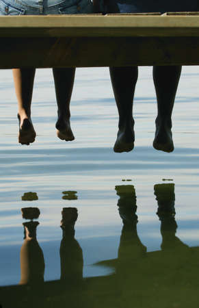 dangling: Two people dangling their feet off a dock