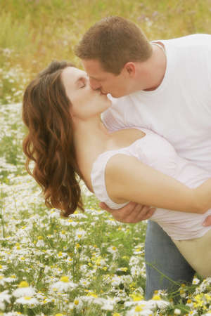 engaged: Couple kiss in a field of daisies Stock Photo
