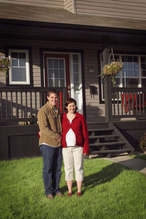 Couple standing in front of new house photo