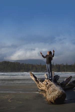 alabanza: Mujer con las manos levantadas en la playa  Foto de archivo