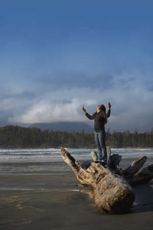 Woman with raised hands on the beach photo