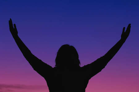 praise: Silhouette of a woman worshipping in nature