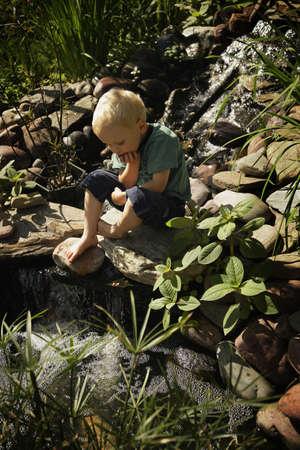 Boy sitting by pond 版權商用圖片