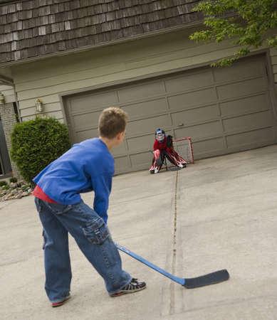 Boys playing hockey on driveway Stock Photo - 7190151