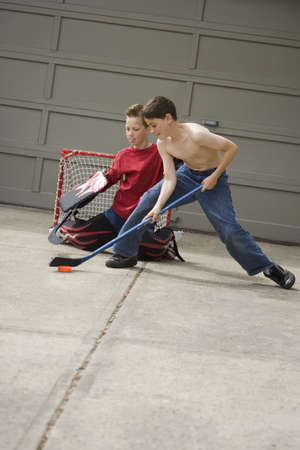 outside shooting: Boys playing hockey on driveway Stock Photo