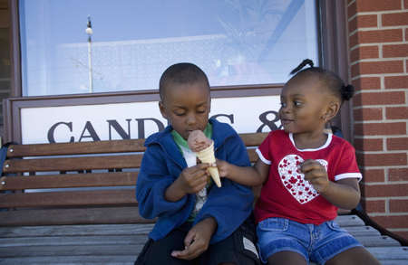 Boy and girl sharing ice cream cone photo