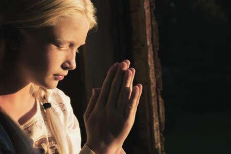belief systems: Girl praying in the dark